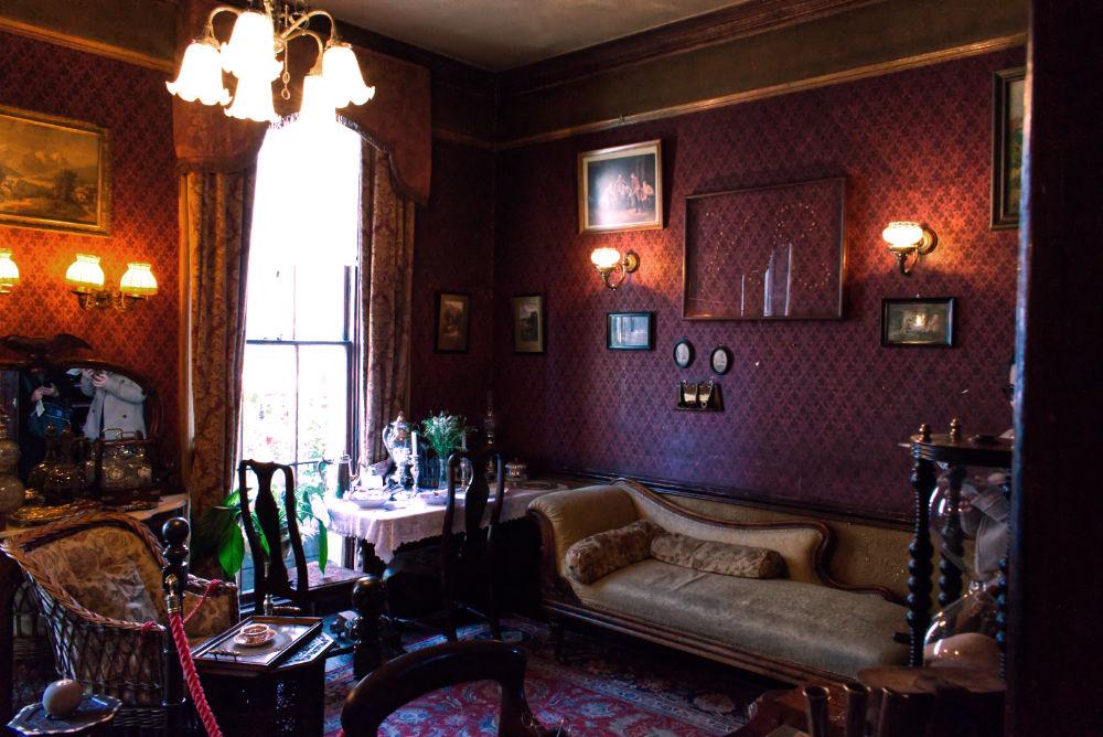 """Intérieur du musée de Sherlock Holmes avec les initiales """"V.R"""" sur le mur dessiné avec des coups de feu"""