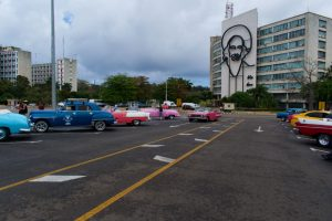 Des taxis typiques de Cuba devant le monument en hommage à Camilo CIenfuegos sur la Place de la Révolution de La Havane à Cuba